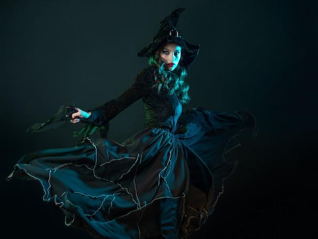 Czarownica w długiej czarnej sukience tańczy i wyczarowuje przyjęcie z okazji halloween