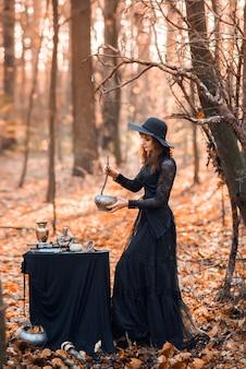Czarownica w jesiennym lesie. kobieta w czarnej długiej sukni gotująca miksturę przygotowuje się do halloween