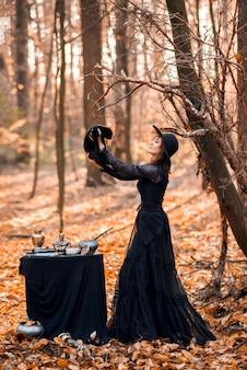 Czarownica w jesiennym lesie. kobieta z czarnym kotem przygotowuje się do halloween.