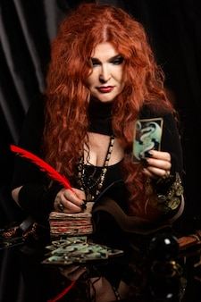 Czarownica, wróżka z rudymi włosami wykonuje magiczny rytuał. czytnik kart.