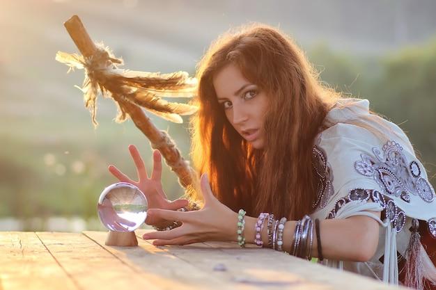 Czarownica z kryształową kulą o zachodzie słońca