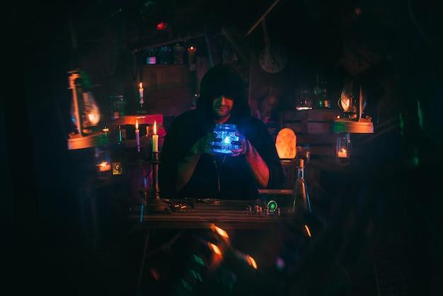 Czarownik alchemik w ciemnych ubraniach zajmuje się wytwarzaniem mikstur w warsztacie rzemieślniczym