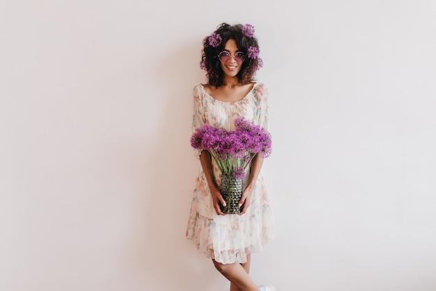 Czarująca afrykańska dama w letniej sukience trzyma wazon z kwiatami. kryty ujęcie inspirowanej kręconej kobiety podczas domowej sesji zdjęciowej.