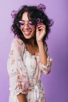 Czarująca afrykańska dziewczyna w okularach bawi się podczas sesji zdjęciowej z sojusznikami. kryty zdjęcie pozytywnej modelki w sukience wyrażającej szczęście.