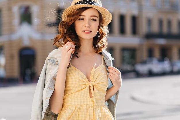 Czarująca biała kobieta nosi letni kapelusz idąc ulicą. imbir ładna dziewczyna w żółtej sukience pozowanie na miasto.