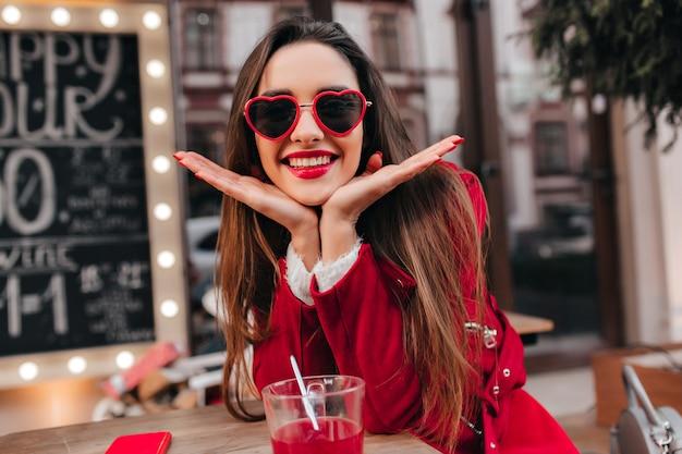 Czarująca biała kobieta pozuje z przyjemnością w kawiarni na świeżym powietrzu