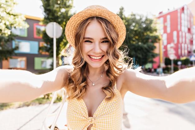 Czarująca blada dziewczyna robi selfie w mieście. zewnątrz zdjęcie wesoła blondynka w żółtym stroju zabawy.