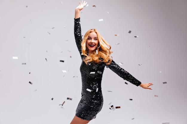 Czarująca blondynka tańczy z zaskoczonym uśmiechem. portret uroczej kaukaskiej kobiety nosi elegancką czarną sukienkę.