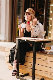 Czarująca blondynka w brązowej czapce vintage, ciesząca się gorącą kawą w zimny dzień. zewnątrz portret radosnej stylowej dziewczyny w eleganckich czarnych sandałach spędzających czas w kawiarni i pijąc herbatę.