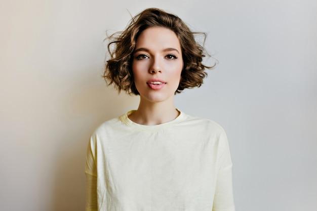 Czarująca brunetka dziewczyna w zwykłej białej koszuli stojącej na jasnej ścianie. romantyczna młoda kobieta z modną fryzurę kręconą