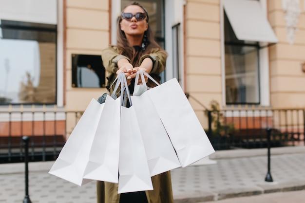 Czarująca ciemnowłosa dama pozuje z całowaniem wyrazem twarzy po zakupach