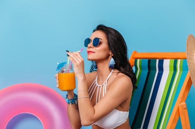 Czarująca dama pije sok pomarańczowy w okularach przeciwsłonecznych