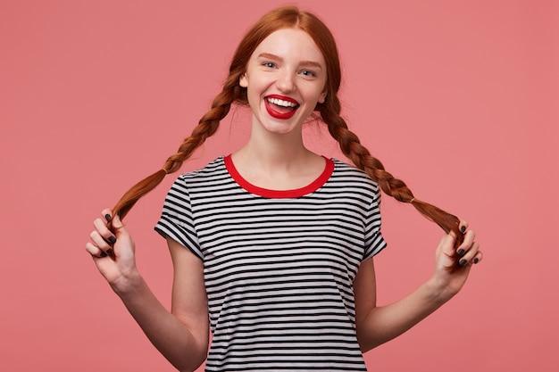 Czarująca dziewczyna trzymająca w rękach dwa rudowłose warkocze, z czerwonymi ustami, ubrana w t-shirt w paski, ubrana w t-shirt w paski