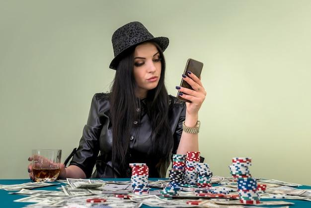 Czarująca dziewczyna w kasynie z telefonem komórkowym mobile
