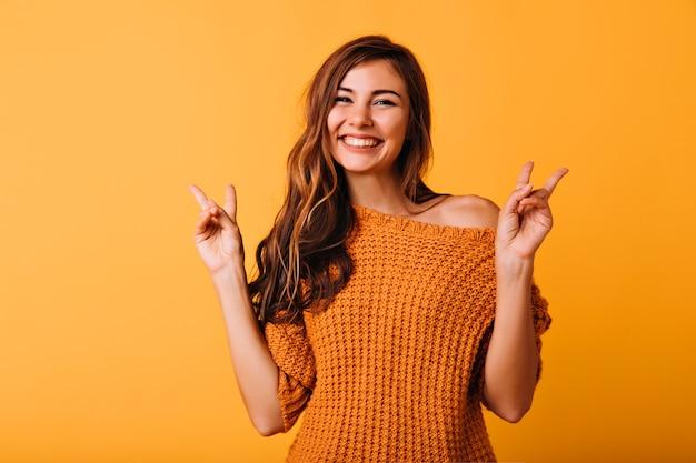 Czarująca dziewczyna z długimi fryzurami pozuje ze znakiem pokoju na pomarańczowo. cieszę się, że modelka w modnym swetrze z dzianiny śmiejąc się w studio.