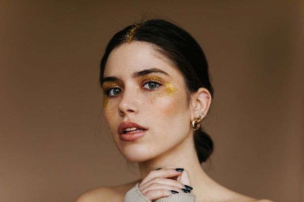 Czarująca dziewczyna ze stylowym złotym makijażem. kryty zbliżenie entuzjastycznej kobiety o czarnych włosach.