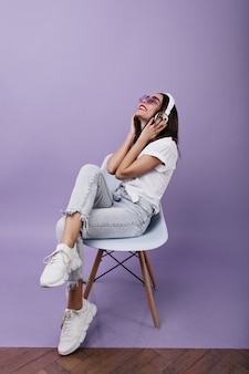 Czarująca europejka w białych tenisówkach słuchająca muzyki. portret szczęśliwa dziewczyna z brązowymi włosami siedzi na krześle ze słuchawkami.