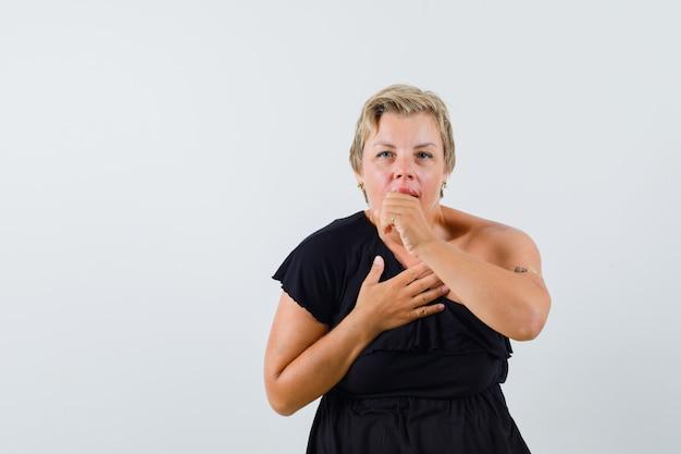 Czarująca kobieta kaszle w czarnej bluzce i wygląda na niekomfortową