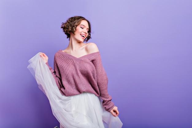 Czarująca kobieta o ciemnych włosach bawi się długą białą spódnicą. wewnątrz portret modnej dziewczyny rasy kaukaskiej nosi fioletowy sweter z dzianiny tańczący z zamkniętymi oczami.