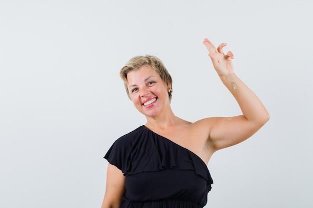 Czarująca kobieta pokazująca gest pożegnania w czarnej bluzce i wyglądająca na zadowoloną