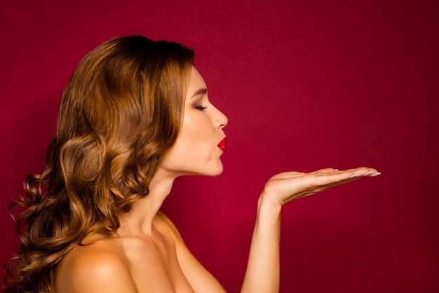 Czarująca kobieta pozuje na czerwonej ścianie