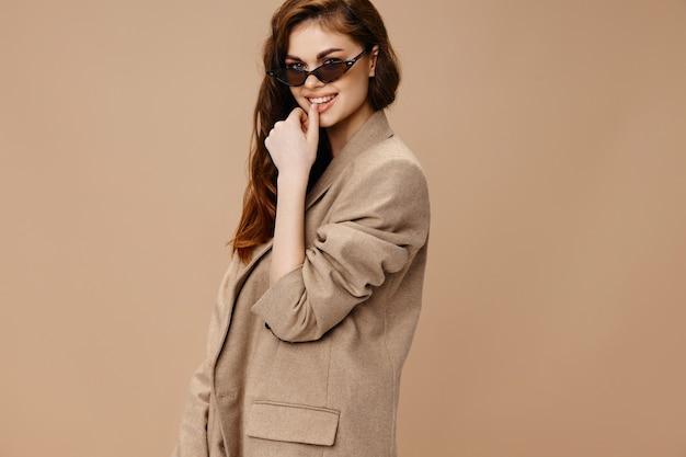 Czarująca kobieta w beżowym płaszczu i okularach uśmiecha się gestykulując rękami