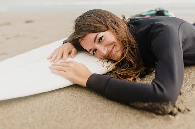 Czarująca kobieta w kombinezonie leżącym na desce surfingowej na plaży w słoneczny, ciepły dzień