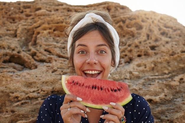 Czarująca młoda ciemnowłosa kobieta w opasce stojąca nad dużym kamieniem i trzymająca w dłoniach kawałek arbuza, ściągająca czoło z szeroko otwartymi ustami