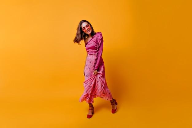 Czarująca młoda kobieta w modnych różowych ubraniach demonstruje swój strój w całej okazałości. brunetka w kolorowych okularach uśmiecha się słodko,