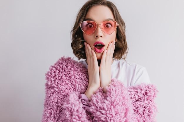 Czarująca młoda kobieta w śmiesznych okularach wyrażająca zdziwienie na białej ścianie. wewnątrz portret zszokowanej kaukaskiej kobiety nosi różowe futro.