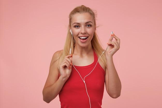Czarująca młoda kobieta z długimi blond włosami, noszenie słuchawek, radośnie patrząc i trzymając słuchawkę, na białym tle