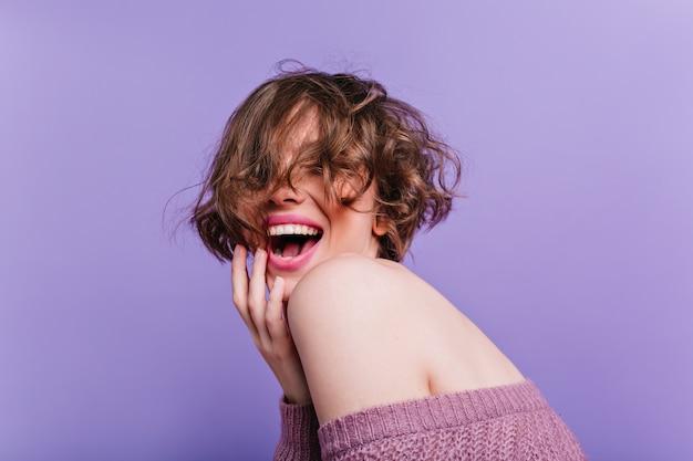 Czarująca modelka z bladą skórą, śmiejąca się na fioletowej ścianie. radosna brunetka dziewczyna gra z jej krótkimi włosami i szczęśliwy, uśmiechnięty.