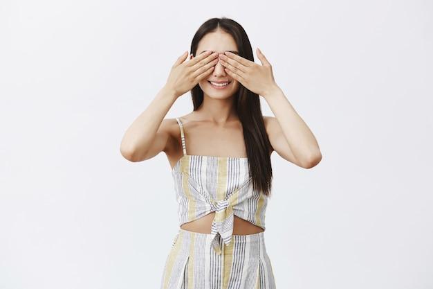 Czarująca modna kobieta w topie i szortach zamykająca oczy dłońmi i szeroko uśmiechnięta, bawiąca się w chowanego lub czekająca niespodzianka z podniecenia