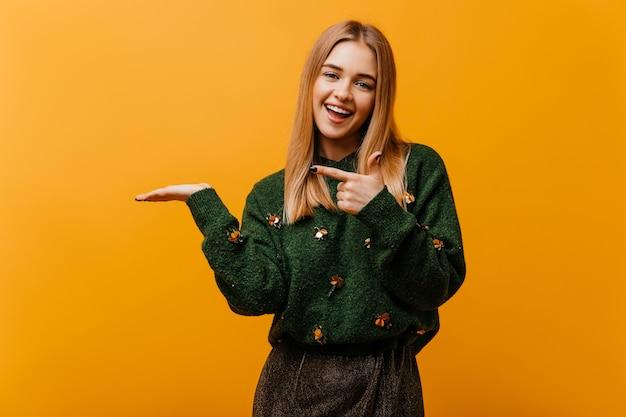 Czarująca niewidoma kobieta w modnym swetrze z dzianiny wyrażającym szczęście. kryty portret uroczej kobiety europejskiej stojącej na pomarańczowo.