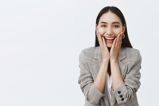 Czarująca podekscytowana dorosła przedsiębiorczyni, uśmiechnięta szeroko z intrygą, trzymająca dłonie na policzkach, z zainteresowaniem wpatrująca się w niesamowite plotki, lubiąca brudne plotki