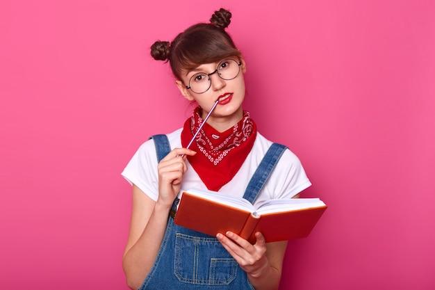 Czarująca, przemyślana studentka w okularach myśli o czymś ważnym, trzyma planistę w rękach, przygotowuje się do egzaminów, trzyma wargę na ustach, pozuje na różowo.