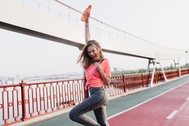 Czarująca zwyciężczyni pozująca po maratonie. zewnątrz portret uroczej dziewczyny wyrażającej pozytywne emocje na stadionie.