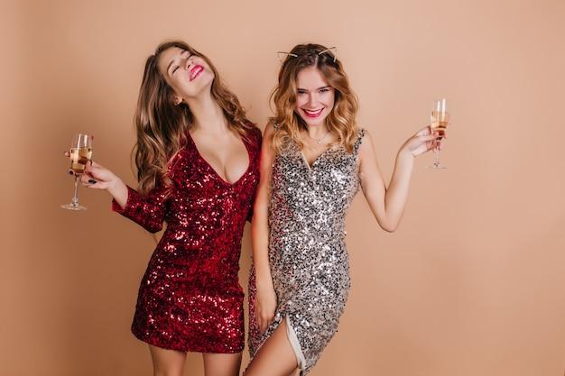 Czarujące kręcone kobiety spędzające czas na przyjęciu noworocznym i delektując się szampanem