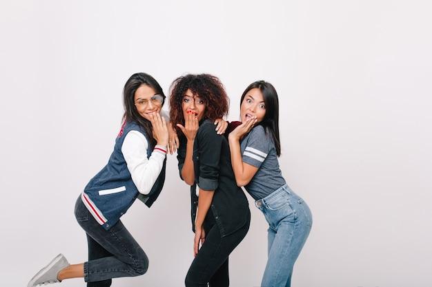 Czarujące międzynarodowe koleżanki w sportowych strojach pozują razem. mulat kręcone dziewczyna w czarnym stroju żartuje z kolegami z uniwersytetu.
