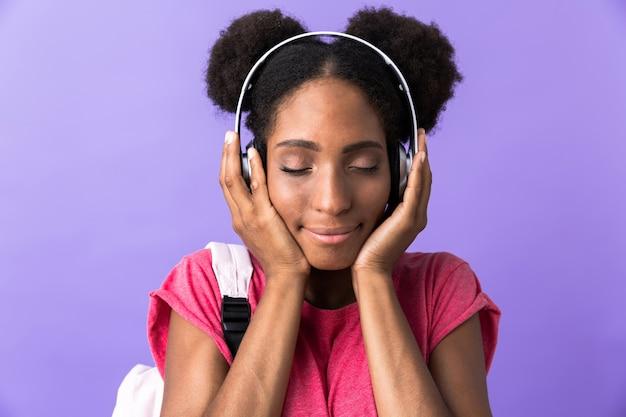 Czarujący african american kobieta na sobie plecak i białe słuchawki, na białym tle