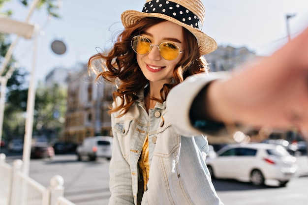 Czarujący kaukaski dziewczyna z czerwonymi kręconymi włosami robi selfie na ulicy. wesoła młoda dama w dżinsowej kurtce, śmiejąc się z miasta.