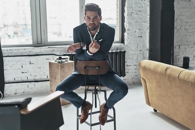 Czarujący mężczyzna. przystojny młody mężczyzna w pełnym garniturze, patrzący w kamerę i uśmiechający się siedząc na stołku