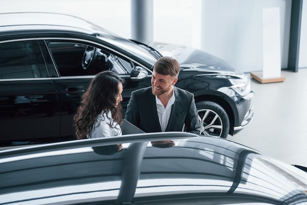 Czarujący młodzi ludzie. żeński klient i nowoczesny stylowy brodaty biznesmen w salonie samochodowym