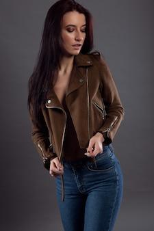 Czarujący portret ładnej brunetki w dżinsach i rozpiętej kurtce na jej nagim seksownym ciele.