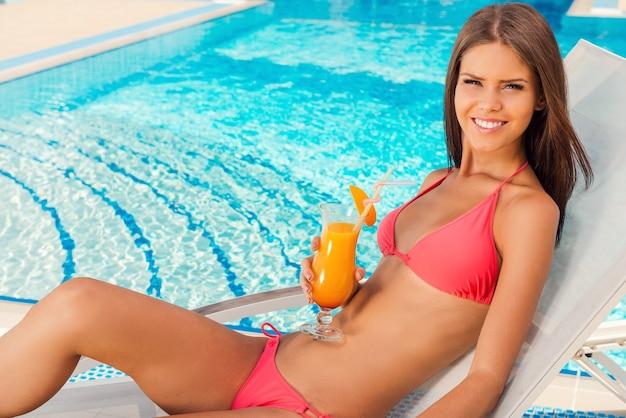 Czas beztroski przy basenie. widok z góry na piękną młodą kobietę w bikini pijącą koktajl i uśmiechającą się podczas relaksu na leżaku przy basenie
