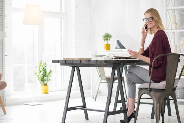 Czas biznesu. ambitna wesoła bizneswoman siedzi na krześle i komunikuje się przez telefon