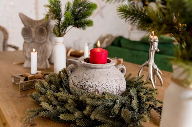 Czas bożego narodzenia, palenie świec z jagodami i zielonymi gałązkami. jasno świecąca świeca. kompozycja ze świecami świątecznymi na drewnianym stole. przygotowanie do imprezy. ręcznie wykonany wystrój domu. ręcznie wykonany wystrój
