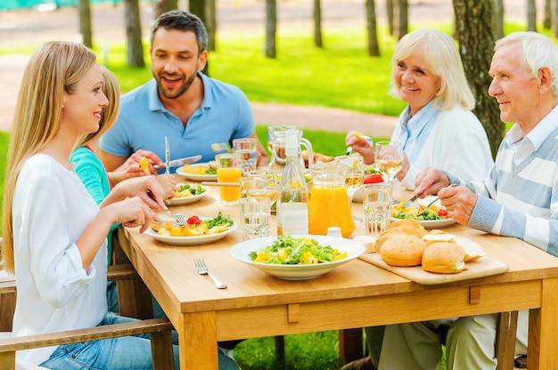 Czas dla rodziny. szczęśliwa rodzina pięciu osób komunikujących się i cieszących się posiłkiem razem, siedząc przy stole na świeżym powietrzu