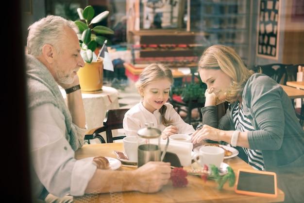 Czas dla rodziny. szczęśliwi współcześni kochający dziadkowie spędzają czas z rodziną z uroczą inteligentną dziewczyną