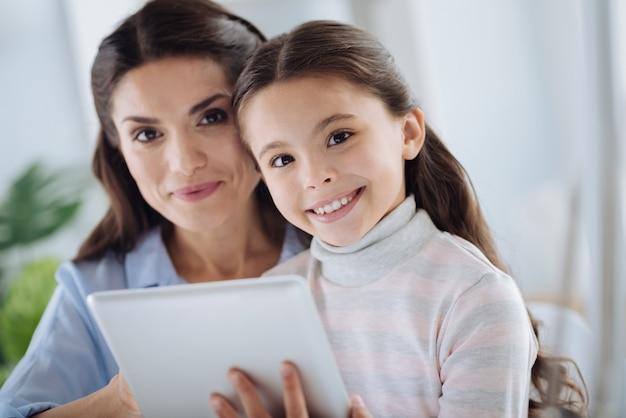 Czas dla rodziny. zadowolony ładny miła dziewczyna trzyma tabletkę i patrzy na ciebie siedząc razem z matką
